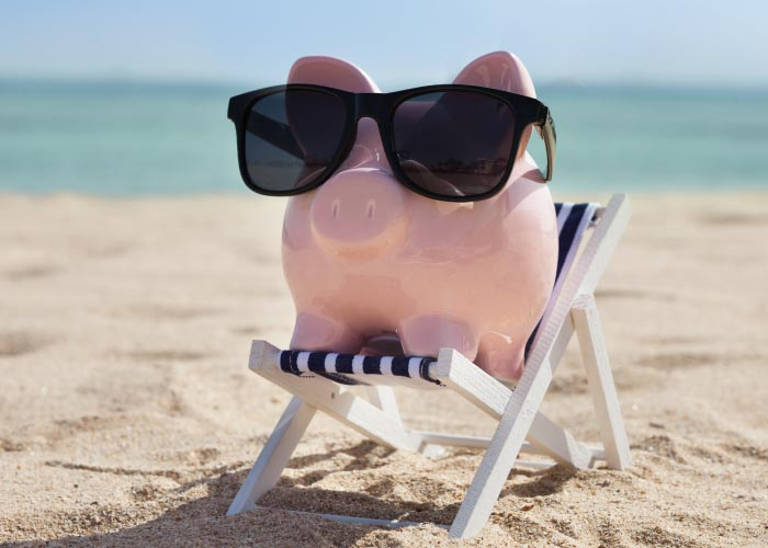A piggy bank with sunglasses on a deckchair